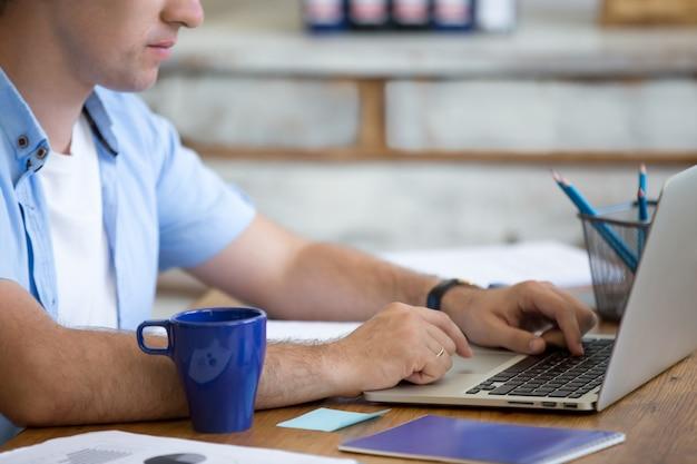 Hombre escribiendo en un portátil
