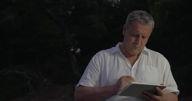 Hombre escribiendo en tableta en crepúsculo