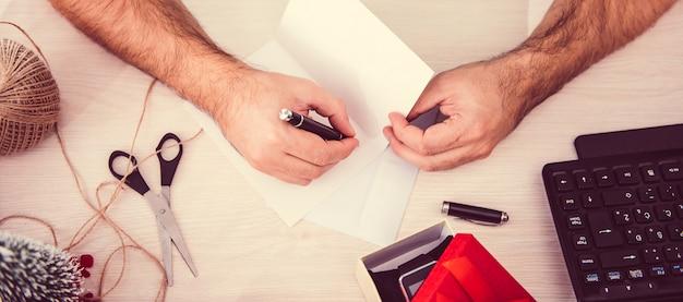 Hombre escribiendo una tarjeta de navidad