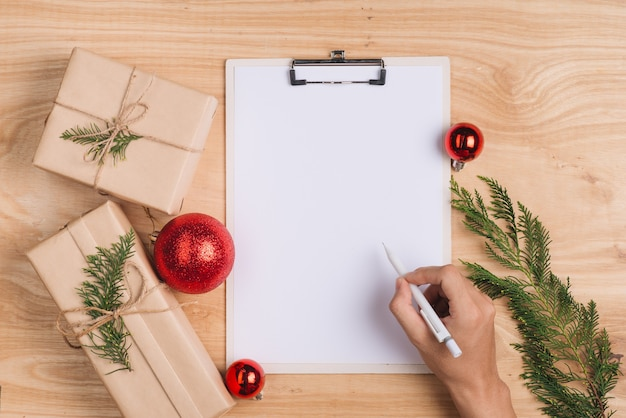 Hombre escribiendo tarjetas de felicitación de navidad y envolviendo regalos de navidad. vista superior con espacio de copia.