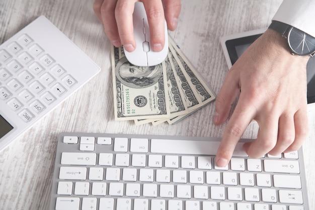 Hombre escribiendo en el teclado. billetes de dólar en el escritorio