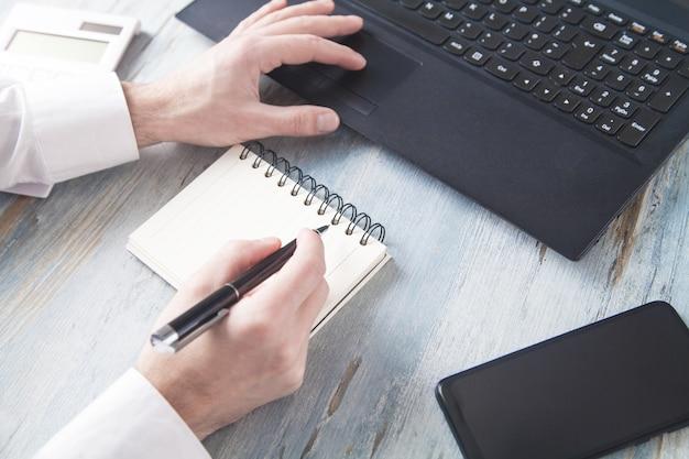 Hombre escribiendo en el teclado y escribiendo en el bloc de notas.