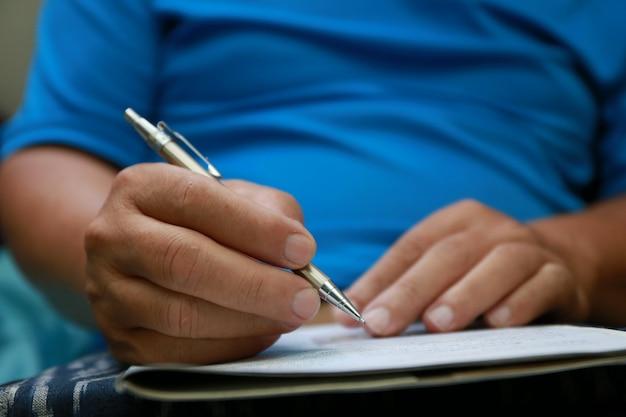 Hombre escribir pluma en papel de documento