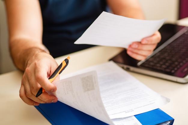 El hombre en un escritorio con documentos trabaja en línea