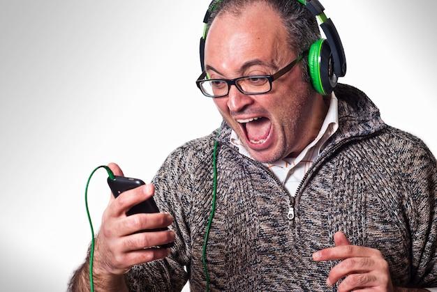El hombre escucha música en los auriculares y grita en voz alta