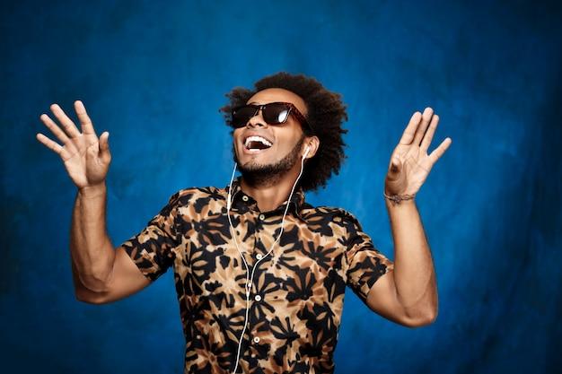 Hombre escuchando música en auriculares, bailando sobre superficie azul