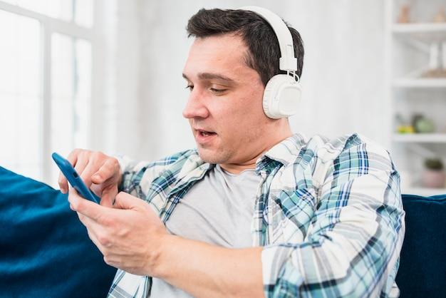Hombre escuchando música en auriculares y navegando en smartphone en sofá