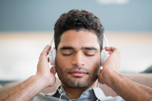 Hombre escuchando música con auriculares en la sala de estar