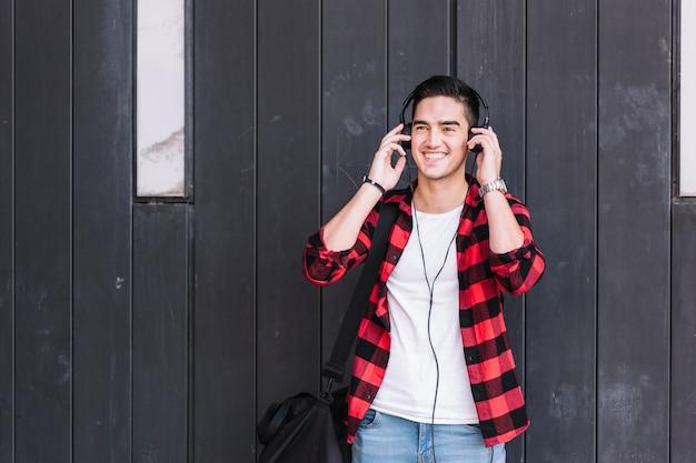 Hombre escuchando música en frente de la pared de madera