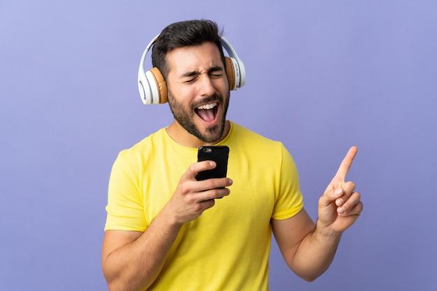 Hombre escuchando música sobre pared aislada