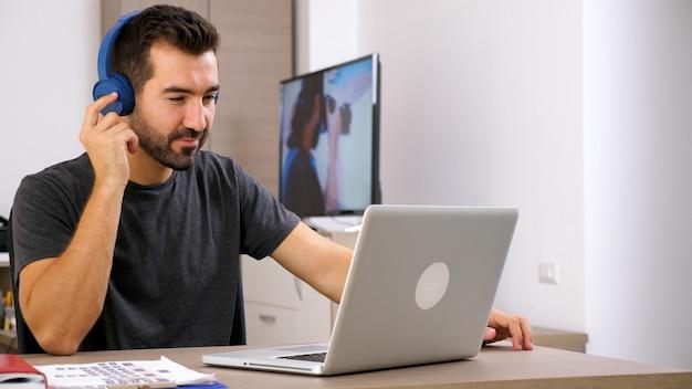 Hombre escuchando música con sus auriculares en la oficina. buena vibra