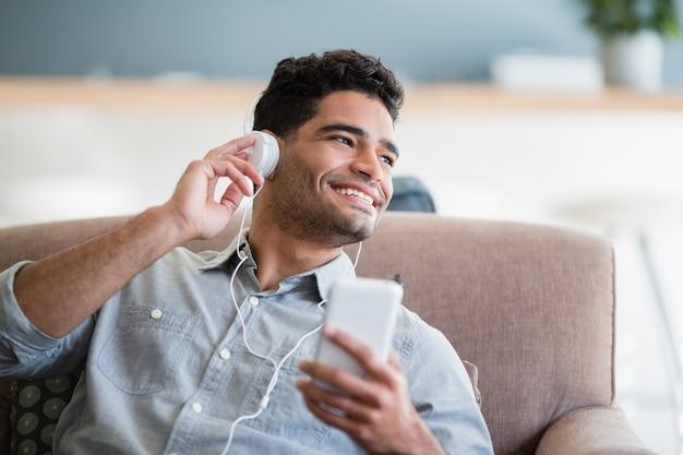 Hombre escuchando música en el teléfono móvil en la sala de estar