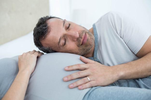 Hombre escuchando el vientre de mujer embarazada en su habitación.