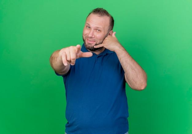Hombre eslavo adulto complacido haciendo gesto de llamada y apuntando aislado en la pared verde con espacio de copia
