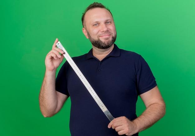 Hombre eslavo adulto complacido sosteniendo medidor de cinta mirando aislado en la pared verde