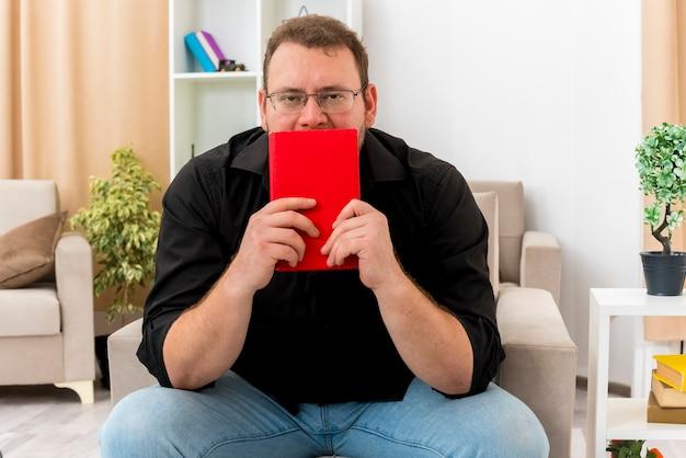 Hombre eslavo adulto confiado en gafas ópticas se sienta en un sillón sosteniendo y mirando por encima del libro dentro de la sala de estar
