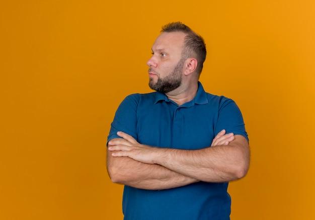 Hombre eslavo adulto de pie con postura cerrada mirando al lado