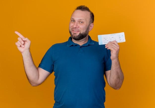 Hombre eslavo adulto sonriente sosteniendo billete de viaje mirando apuntando al lado