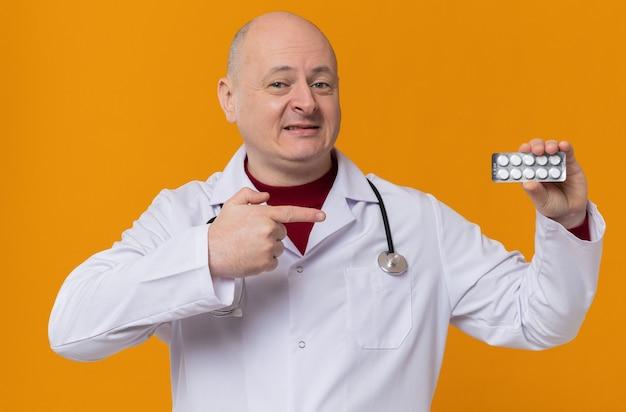 Hombre eslavo adulto sonriente en uniforme médico con estetoscopio sostiene y apunta en el blister de la medicina