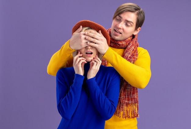 Hombre eslavo guapo complacido con bufanda alrededor del cuello cerrando los ojos de una mujer bonita rubia con boina en el día de san valentín