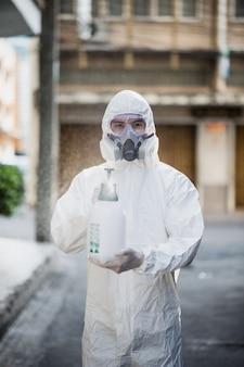 Hombre especialista en desinfección con traje de equipo de protección personal (epi), guantes, mascarilla y protector facial, limpieza del área de cuarentena con una botella de desinfectante en aerosol presurizado para eliminar el coronavirus