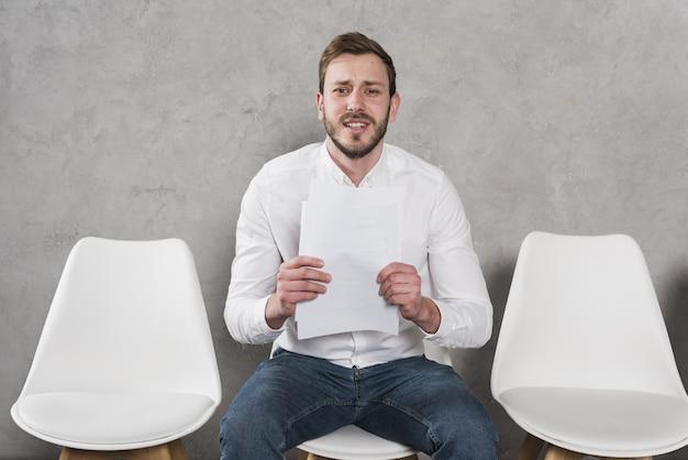 Hombre esperando su entrevista de trabajo y con currículum
