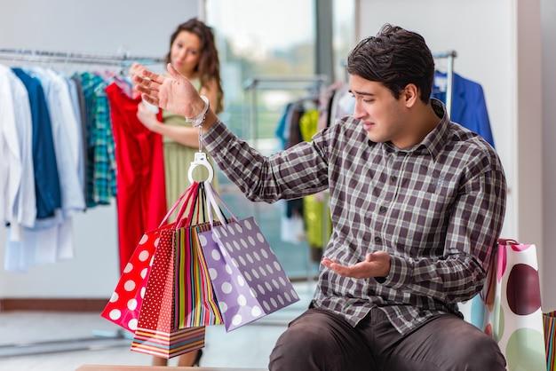 Hombre esperando a su esposa durante las compras navideñas
