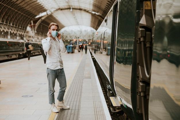Hombre esperando un tren en una plataforma