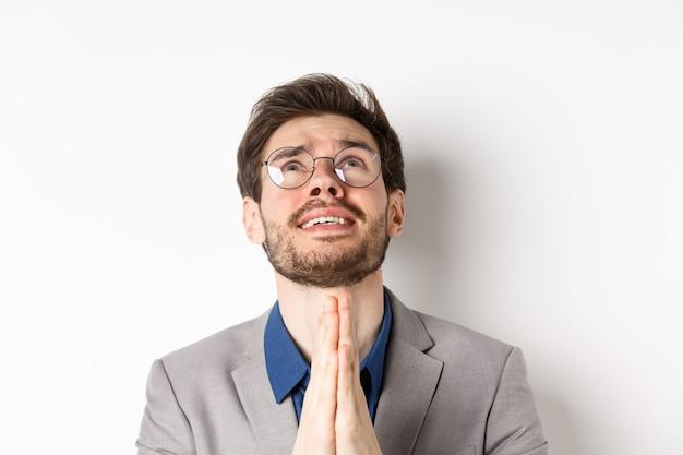 Hombre esperanzado nervioso con gafas y traje rogando a dios, pidiendo por favor y estrechándole la mano en oración, fondo blanco.
