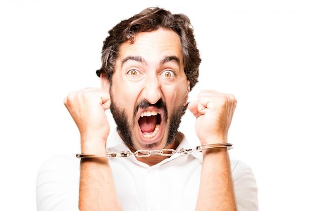 Hombre esposado con unas esposas de policía y gritando
