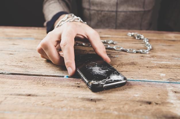 Un hombre esposado sosteniendo un teléfono roto.