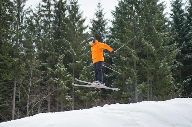 Hombre esquiador volador al saltar desde la ladera de las montañas