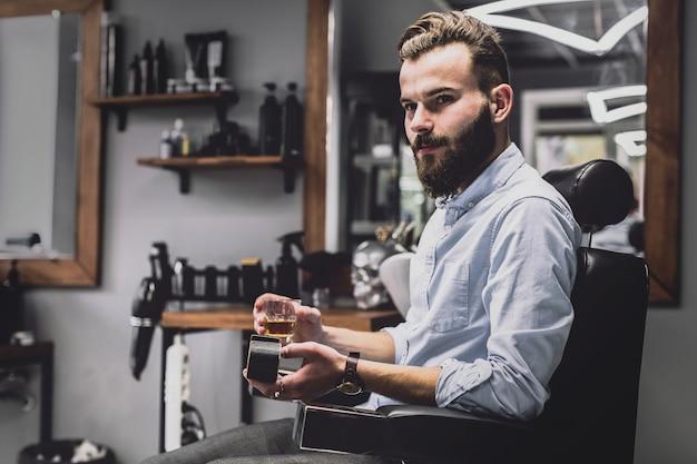 Hombre con estilo con bebida de alcohol en peluquería