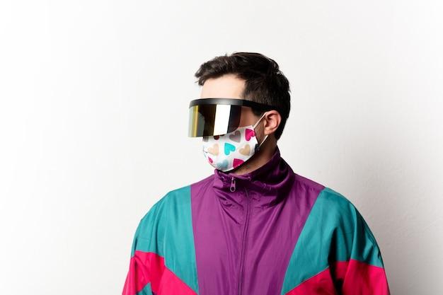 Hombre de estilo en chándal y gafas futuristas.