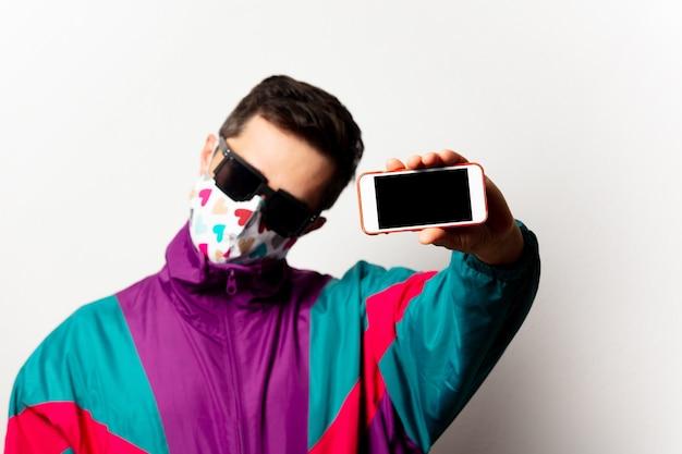 Hombre de estilo en chándal y gafas de sol con teléfono móvil
