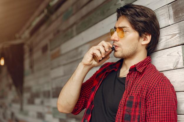 Hombre con estilo y elegante en una ciudad con vape