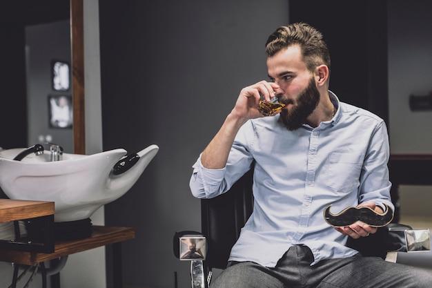 Hombre con estilo que beber en barbería