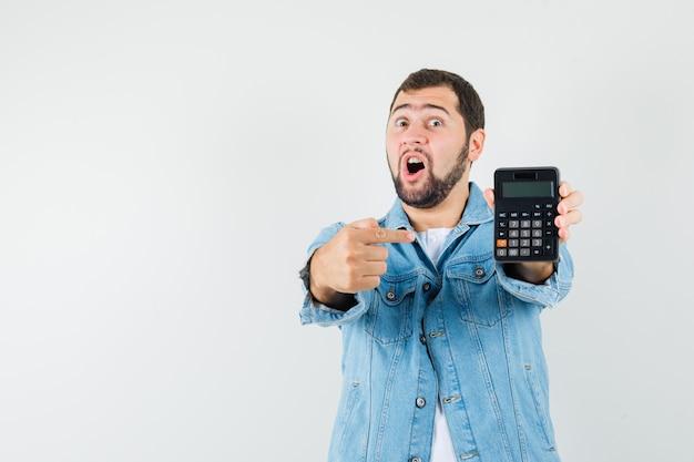 Hombre de estilo retro apuntando a la calculadora en chaqueta, camiseta y mirando perplejo. vista frontal. espacio para texto