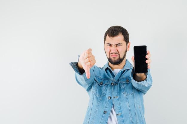 Hombre de estilo retro que muestra el pulgar hacia abajo mientras muestra el teléfono móvil con chaqueta, camiseta y aspecto negativo. vista frontal.