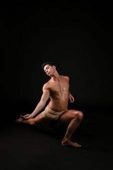 Hombre estirando apoyándose en la rodilla levantando la mano al lado