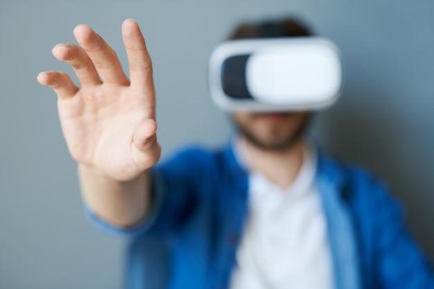 Hombre estirando la mano en realidad virtual