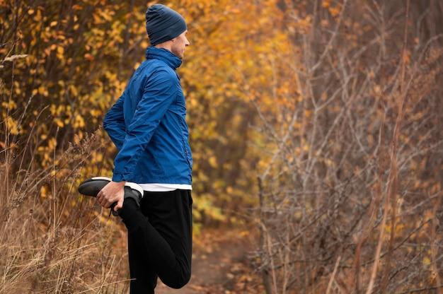 Hombre estirando sus piernas en el bosque