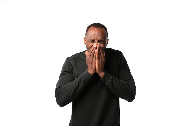 Hombre estornudando en la pared blanca