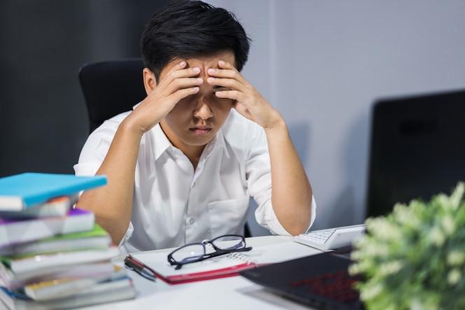 Hombre estresado estudiando con libro y computadora portátil