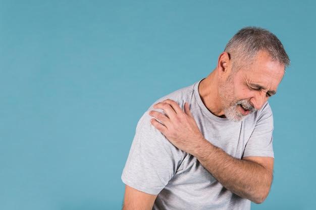 Hombre estresado senior con dolor en el hombro sobre fondo azul