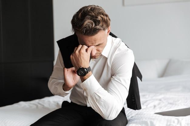 Hombre estresado vestido con traje sentado en la cama