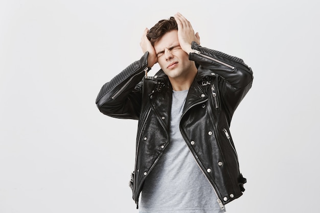 Hombre estresante y guapo vestido con una chaqueta de cuero negro grita de pánico, cierra los ojos aterrorizado, mantiene las manos en la cabeza, descubre malas noticias o desastres sobre su mejor amigo. gente, estrés, molestia.