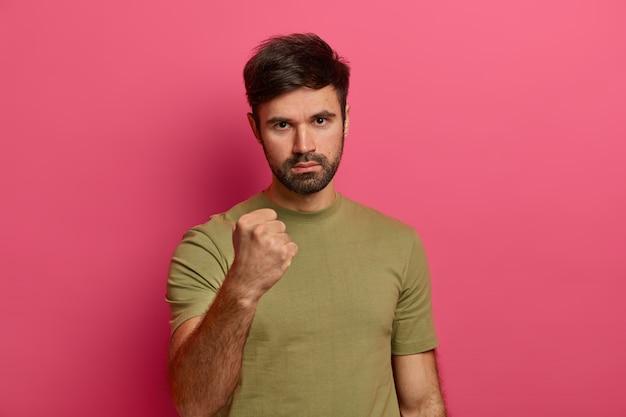 Hombre estricto enojado con barba espesa, furioso, expresa advertencia y amenaza