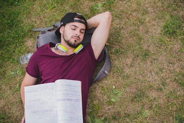 Hombre estudiante acostado en la hierba durmiendo