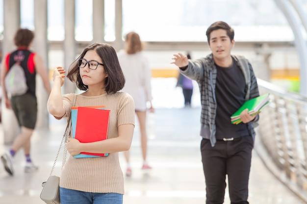 Hombre estudiante corriendo tratar de llegar a su amigo durante holdinh libros en las manos